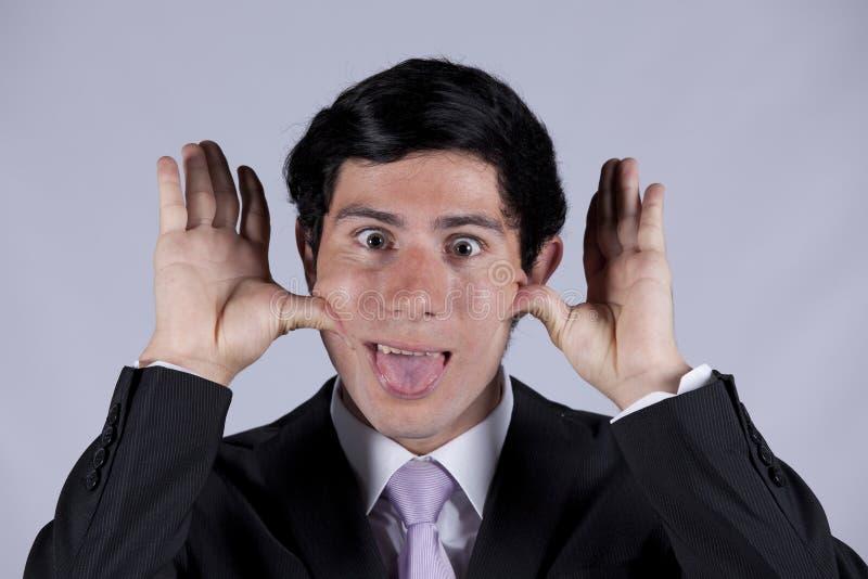 Jeune homme d'affaires avec un visage drôle photographie stock libre de droits