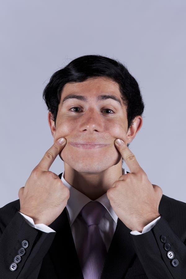Jeune homme d'affaires avec un visage drôle images stock