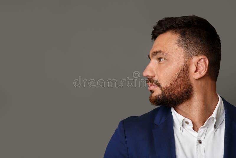 Jeune homme d'affaires barbu élégant de pensée regardant loin photographie stock libre de droits