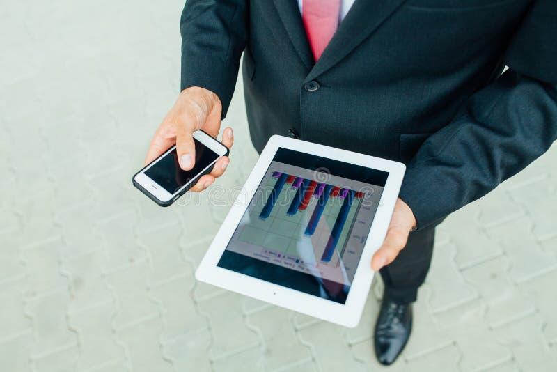 Jeune homme d'affaires barbu analysant des diagrammes sur le PC et le mobi de comprimé photographie stock libre de droits