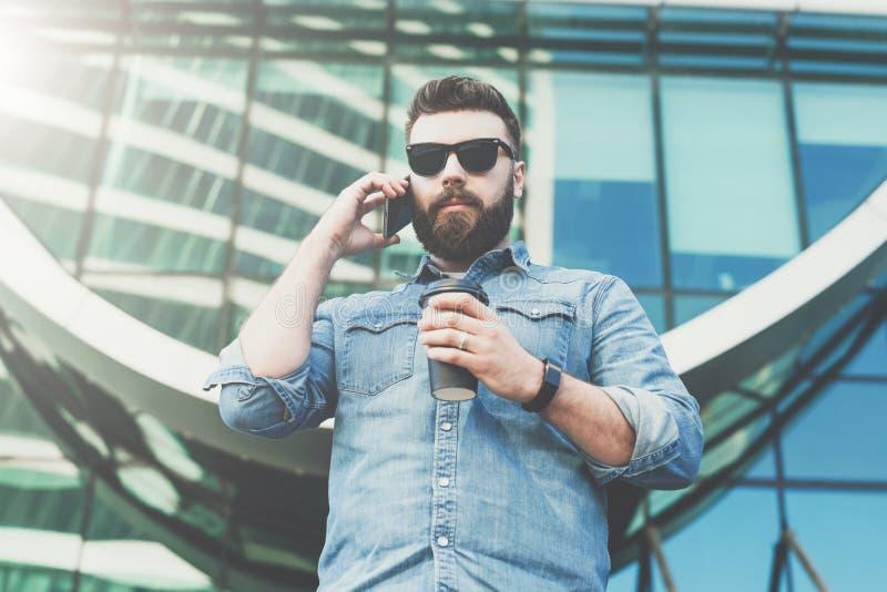 Jeune homme d'affaires barbu de hippie dans les lunettes de soleil et les supports extérieurs, café potable et entretiens à son t photographie stock libre de droits