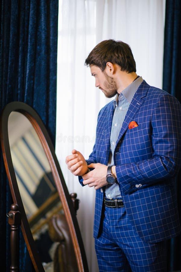 Jeune homme d'affaires barbu essayant sur le costume fait sur commande, boutonnant la veste image stock