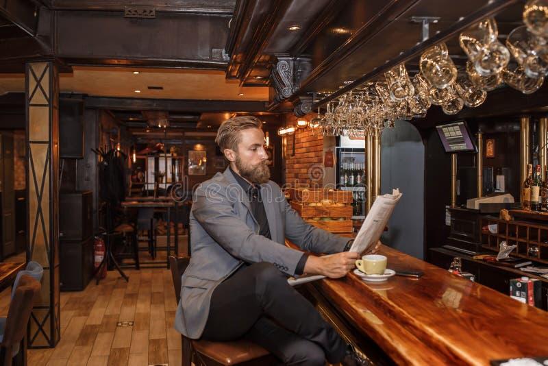Jeune homme d'affaires barbu lisant un journal photo stock