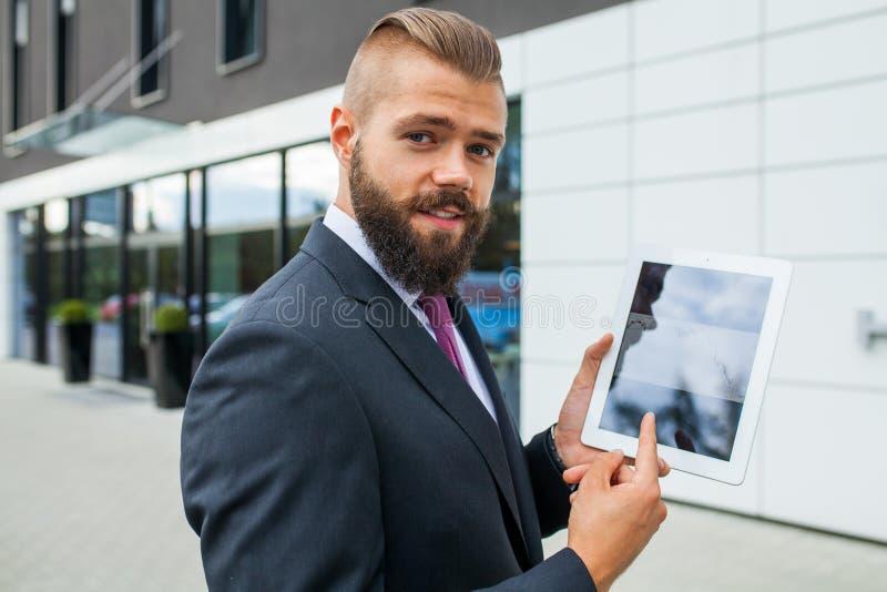 Jeune homme d'affaires barbu montrant des diagrammes sur le PC de comprimé P extérieur photos stock