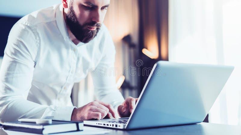 Jeune homme d'affaires barbu sérieux se tenant dans le bureau près de la table et à l'aide de l'ordinateur portable L'homme trava images stock