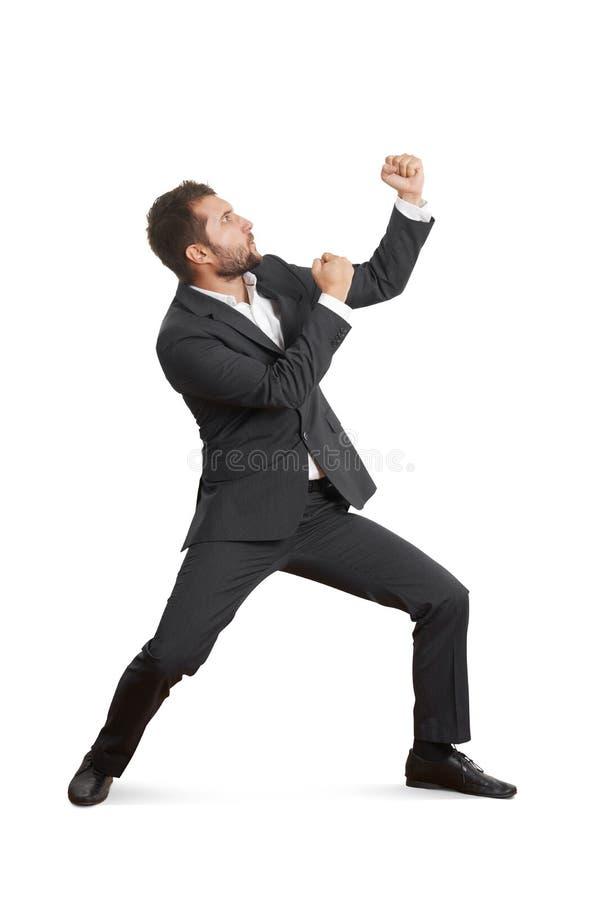 Jeune homme d'affaires battant son poing photographie stock