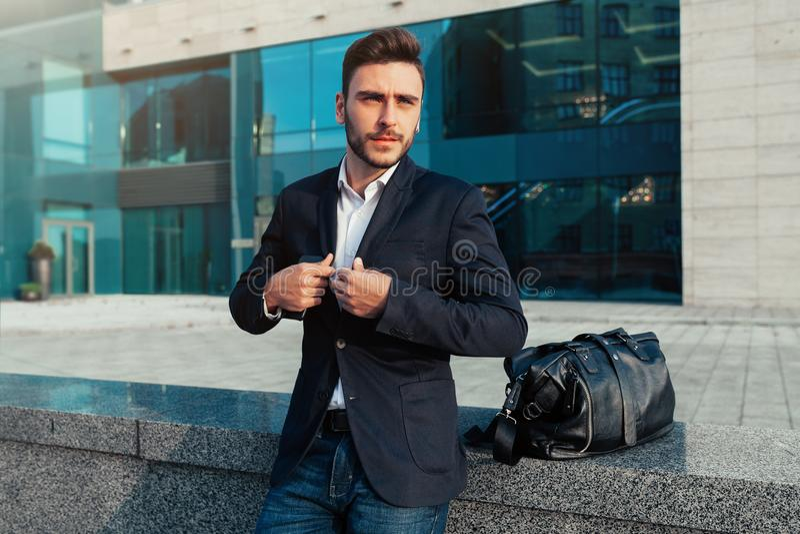 Jeune homme d'affaires beau avec une barbe et dans une position de costume sur la rue images libres de droits