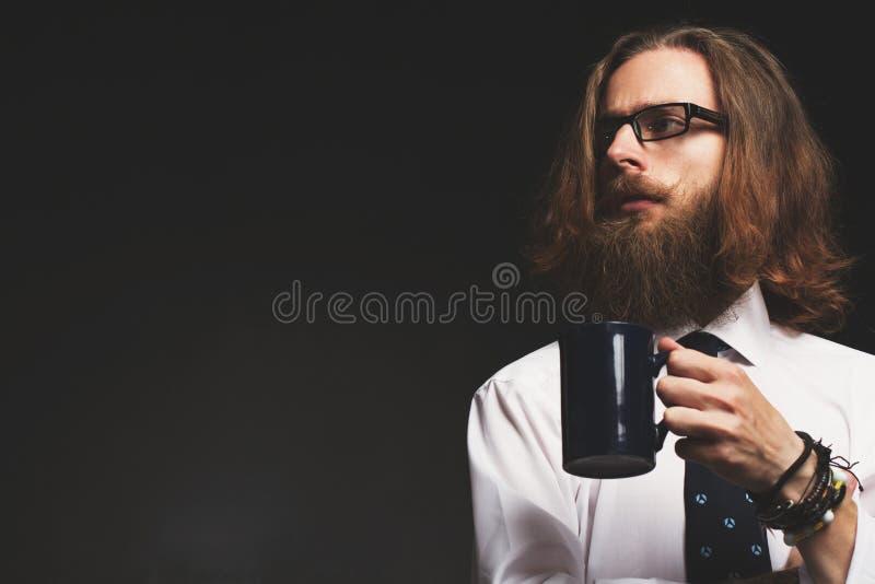 Jeune homme d'affaires beau de hippie avec une tasse de café sur le mur noir image stock