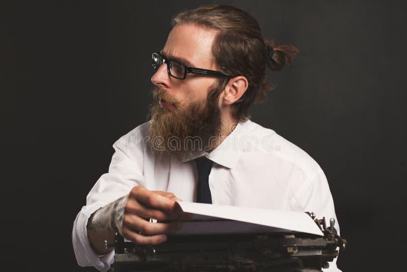 Jeune homme d'affaires beau de hippie pensant et écrivant avec la machine à écrire de cru photo libre de droits