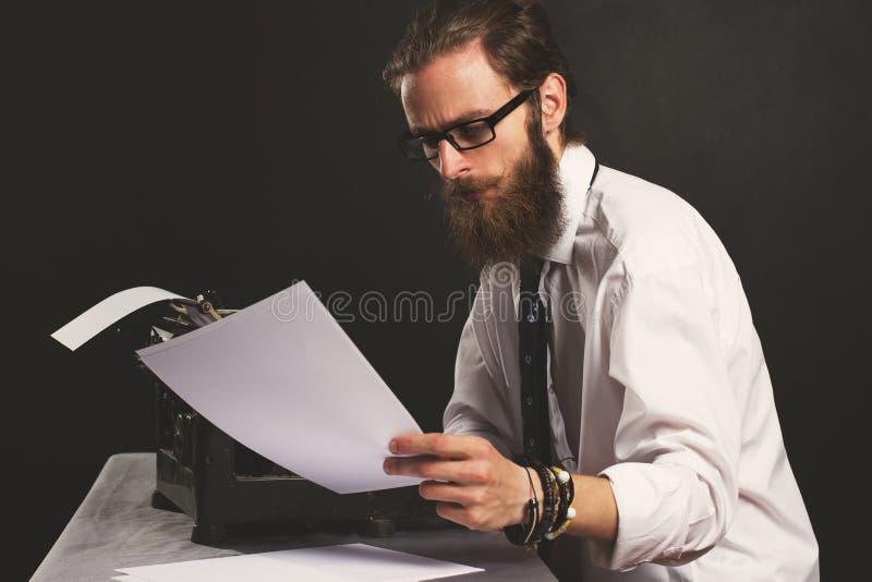 Jeune homme d'affaires beau de hippie pensant et écrivant avec la machine à écrire de cru photos libres de droits