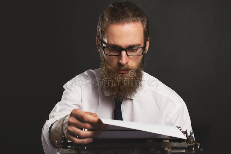 Jeune homme d'affaires beau de hippie pensant et écrivant avec la machine à écrire de cru images stock