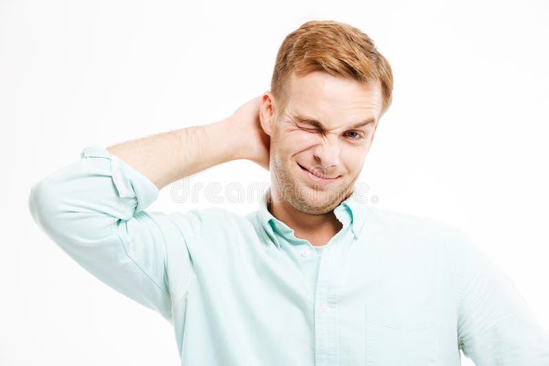 Jeune homme d'affaires beau paresseux tenant et rayant sa tête photo libre de droits