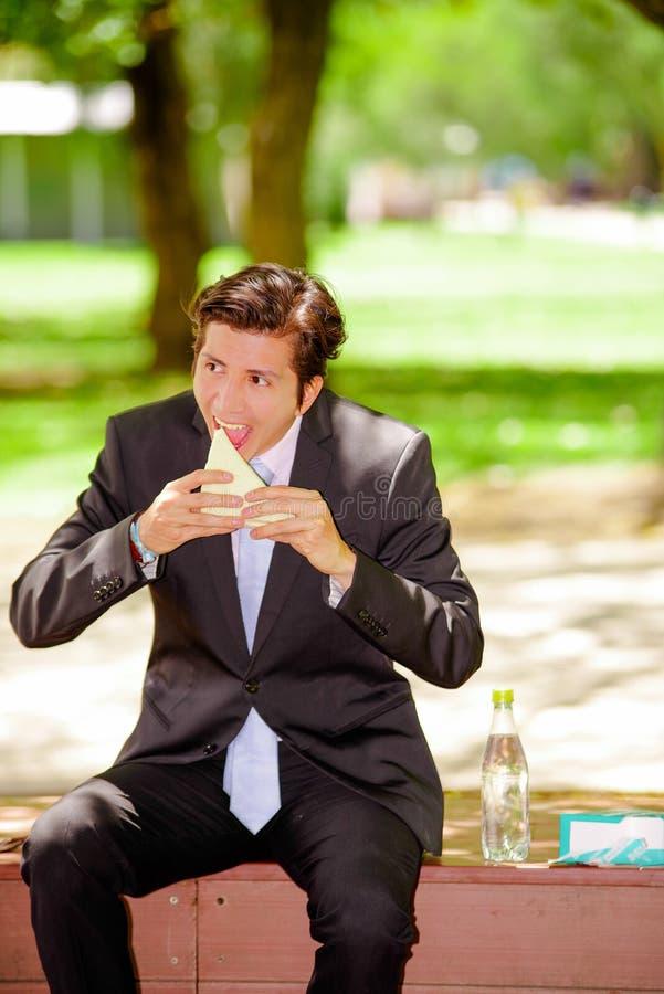 Jeune homme d'affaires beau portant un costume et faisant une morsure énorme mangeant un sandwich à l'extérieur, en parc brouillé photo stock