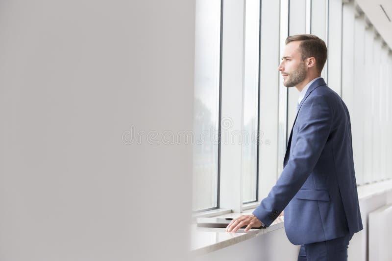 Jeune homme d'affaires beau réfléchi regardant par la fenêtre dans le nouveau bureau photos libres de droits