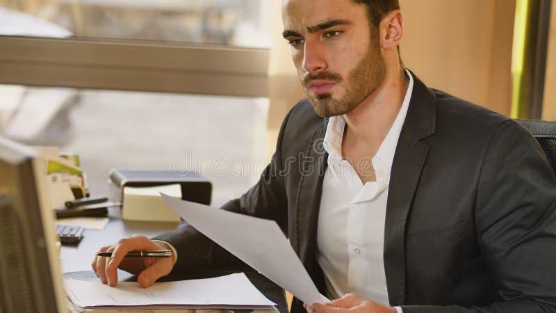 Jeune homme d'affaires beau s'asseyant au bureau dans le bureau image stock