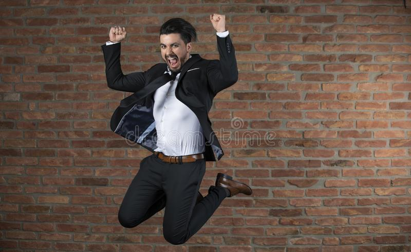Jeune homme d'affaires beau sautant dans le ciel dans un studio photos stock