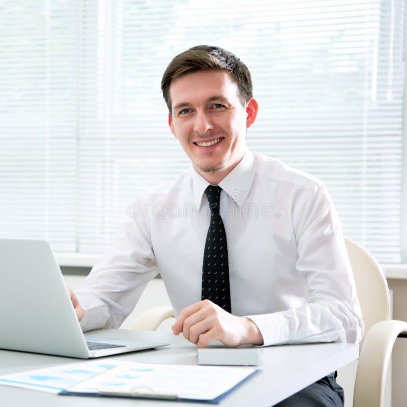 Jeune homme d'affaires beau travaillant à l'ordinateur portable photographie stock