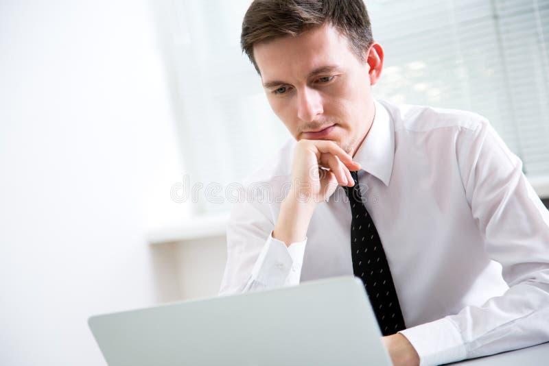 Jeune homme d'affaires beau travaillant à l'ordinateur portable images libres de droits
