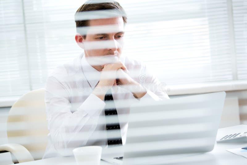 Jeune homme d'affaires beau travaillant à l'ordinateur portable dans le bureau image libre de droits