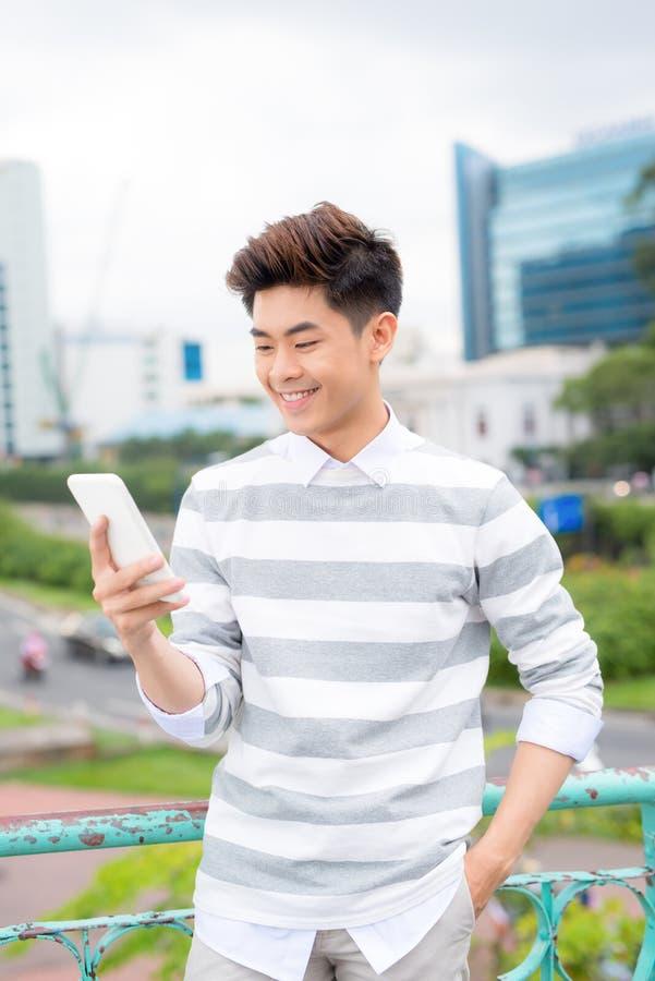 Jeune homme d'affaires bel asiatique souriant tout en lisant son smartphone Portrait de message asiatique de lecture d'homme d'af image stock
