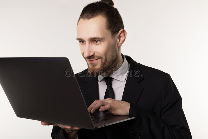 Jeune homme d'affaires bel avec la barbe et la coiffure à la mode portant le costume et la cravatte noirs photos libres de droits