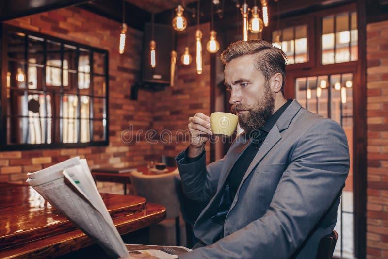 Jeune homme d'affaires bel lisant un journal images libres de droits