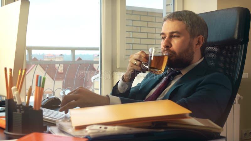 Jeune homme d'affaires caucasien ayant la petite pause sur son lieu de travail Thé potable images libres de droits