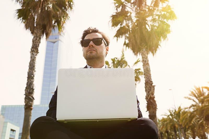 Jeune homme d'affaires caucasien dans des vêtements formels fonctionnant au jour ensoleillé sur l'herbe verte sur l'ordinateur po photos stock