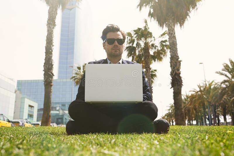 Jeune homme d'affaires caucasien dans des vêtements formels fonctionnant au jour ensoleillé sur l'herbe verte sur l'ordinateur po photo libre de droits