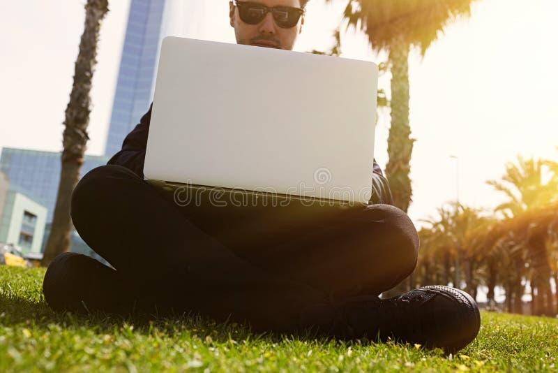 Jeune homme d'affaires caucasien dans des vêtements formels fonctionnant au jour ensoleillé sur l'herbe verte sur l'ordinateur po images libres de droits