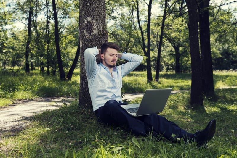Jeune homme d'affaires caucasien travaillant à l'herbe en parc public avec l'ordinateur portable photos stock