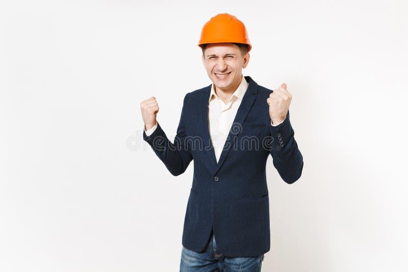 Jeune homme d'affaires comblé bel dans le costume foncé, masque orange protecteur faisant le geste de gagnant, dire oui d'isoleme photographie stock