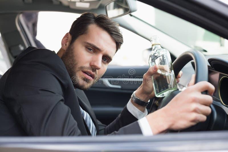 Jeune homme d'affaires conduisant tandis qu'ivre photographie stock