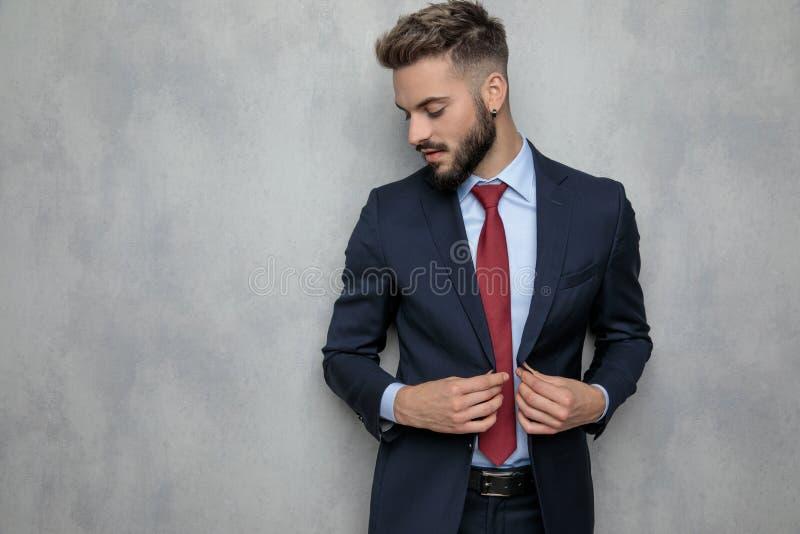 Jeune homme d'affaires déboutonnant ses sourires et regards de manteau vers le bas photographie stock