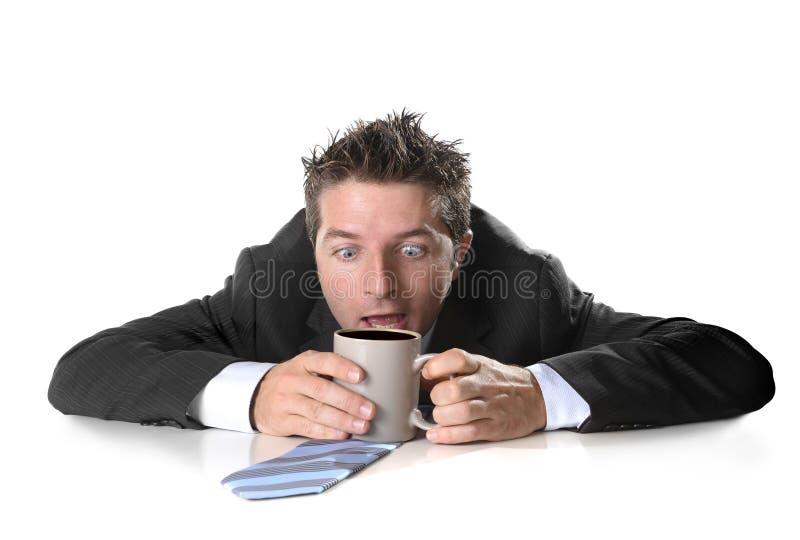Jeune homme d'affaires d'intoxiqué jugeant la tasse de café folle dans la dépendance de caféine photos libres de droits