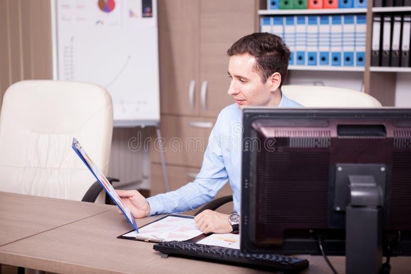 Jeune homme d'affaires dans le bureau analysant des diagrammes image stock
