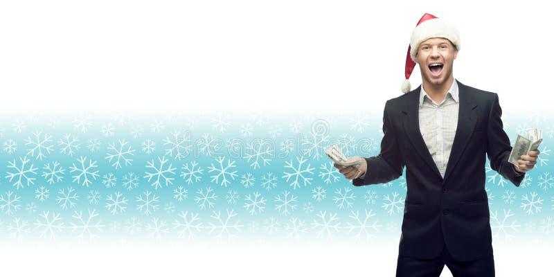 Jeune homme d'affaires dans le chapeau de Santa tenant l'argent au-dessus du backgr d'hiver image libre de droits