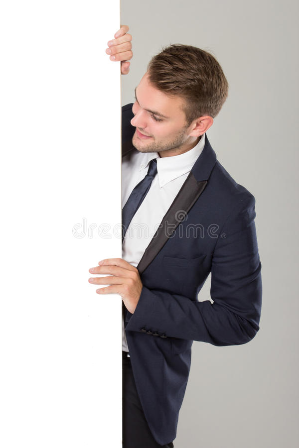 Jeune homme d'affaires dans le costume noir regardant le tableau blanc vide photographie stock libre de droits