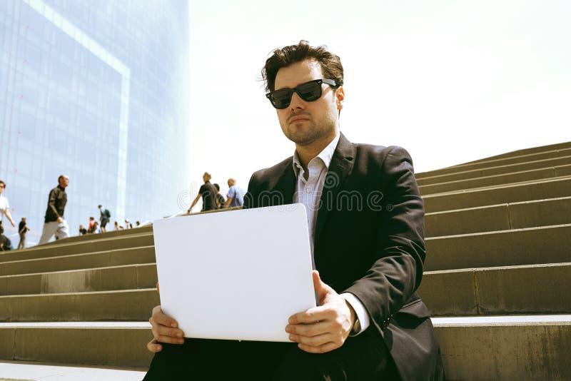 Jeune homme d'affaires dans le formalwear dactylographiant sur le clavier d'ordinateur portable tout en se reposant à hors du bur image stock