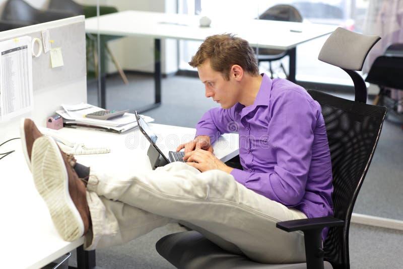 Jeune homme d'affaires dans son bureau fonctionnant avec le comprimé - mauvaise position d'assise photos libres de droits