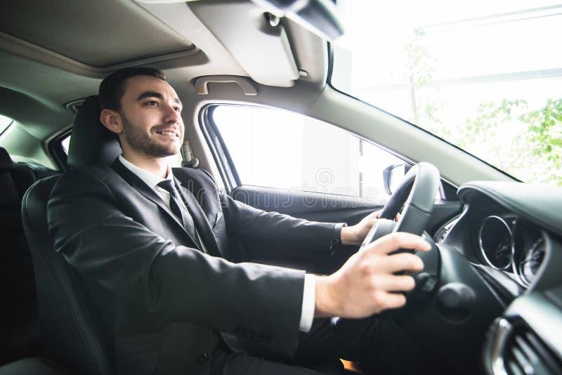 Jeune homme d'affaires dans son véhicule Conducteur de voiture luxuty Voiture belle d'entraînement d'homme photos stock
