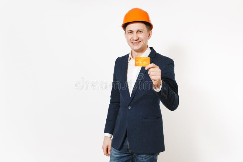 Jeune homme d'affaires de sourire bel dans le costume foncé, casque orange de construction protectrice jugeant la carte de crédit images libres de droits