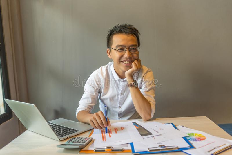 Jeune homme d'affaires de sourire s'asseyant sur le lieu de travail avec les documents et l'ordinateur portable image stock