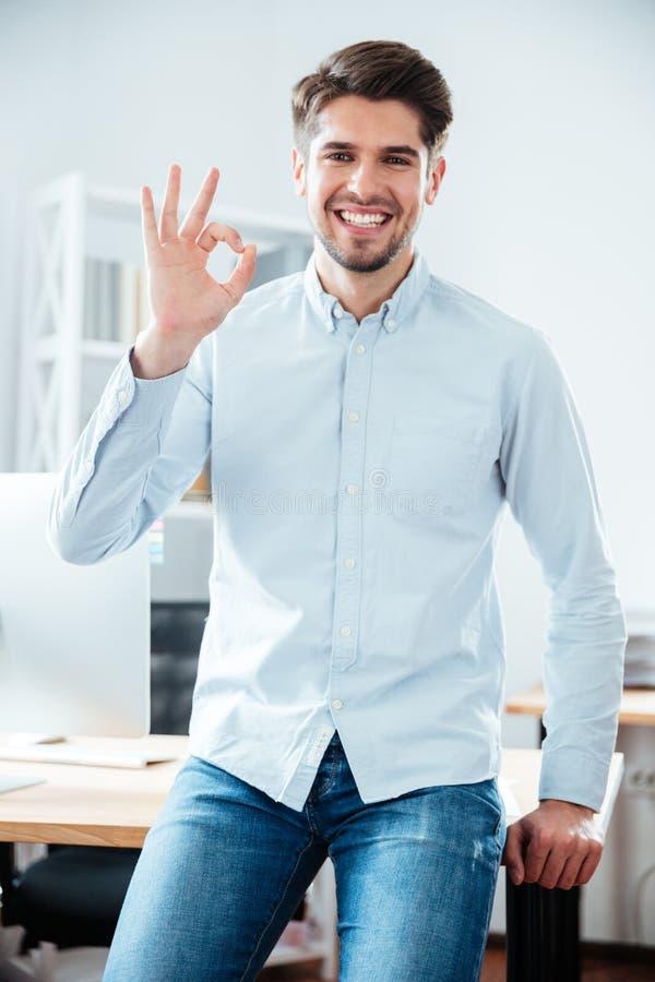 Jeune homme d'affaires de sourire tenant et montrant le signe correct photos stock