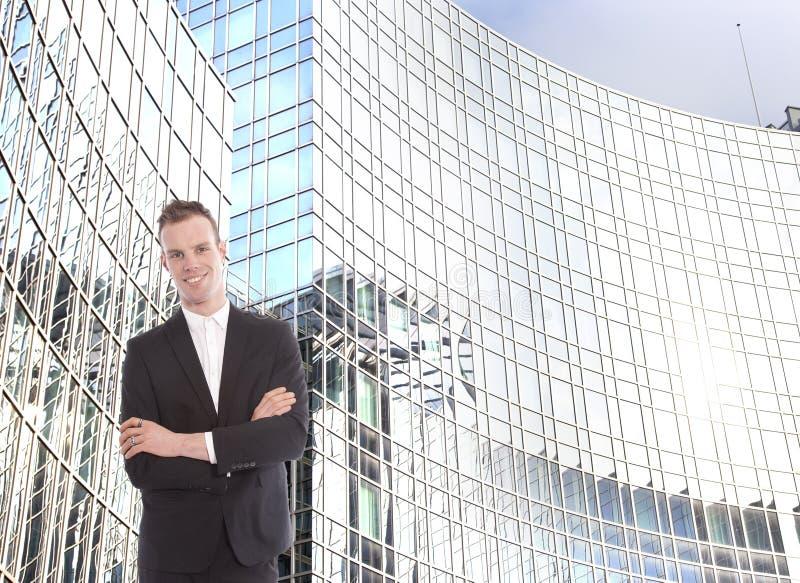 Jeune homme d'affaires devant l'immeuble de bureaux image stock