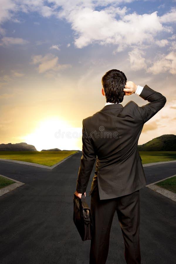 Jeune homme d'affaires devant un carrefour images libres de droits