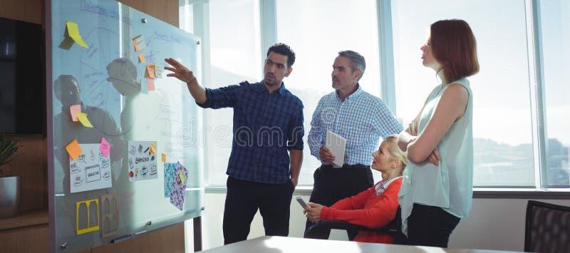 Jeune homme d'affaires discutant avec des collègues au bureau images stock