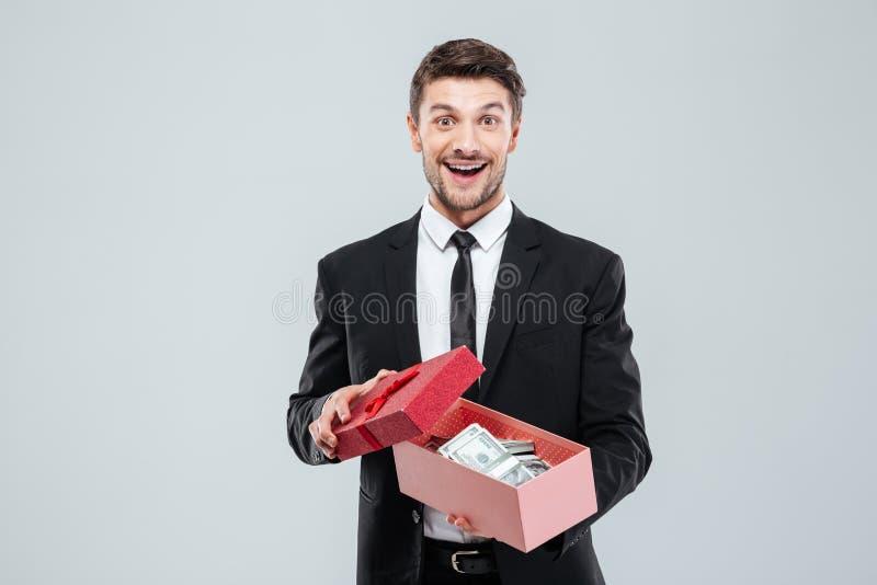 Jeune homme d'affaires enthousiaste heureux jugeant le boîte-cadeau plein de l'argent image stock