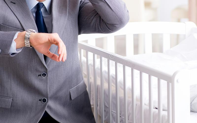 Jeune homme d'affaires essayant de travailler de la maison s'inqui?tant apr?s nouveau-n? photographie stock libre de droits