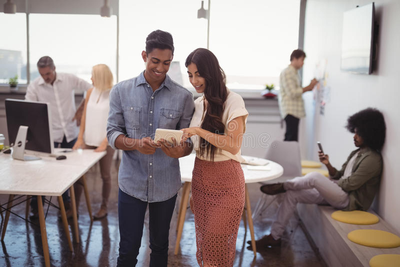 Jeune homme d'affaires et femme d'affaires discutant au-dessus du comprimé numérique avec des collègues à l'arrière-plan images stock
